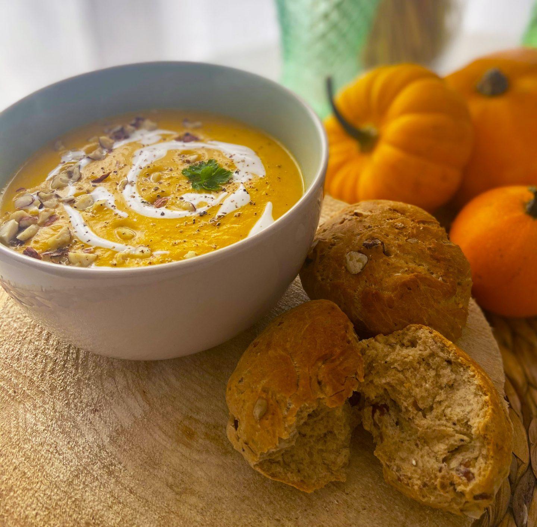 Image pour illustrer la recette, soupe butternut et ses petits pains aux noix. Prêts à la dégustation, il y a des citrouilles en arrière plan pour l'aspect automnal.